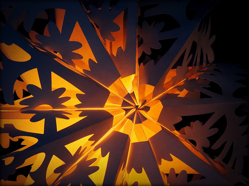 Christmas decoration of a snowflake made of folded paper with cut-outs
