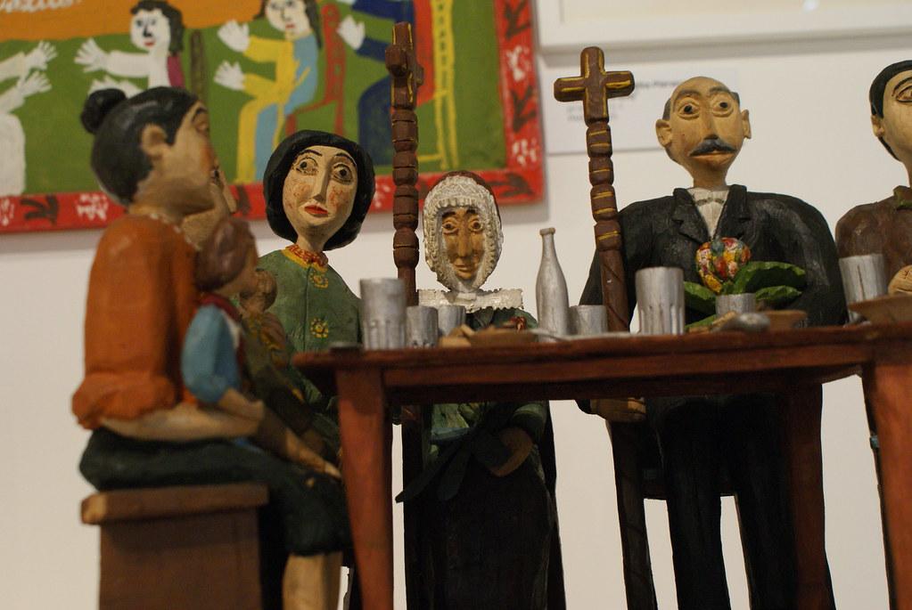 Repas familial de personnages en bois dans le musée ethnographique de Varsovie : On se croirait dans un mélange de Kantor et de Kafka.