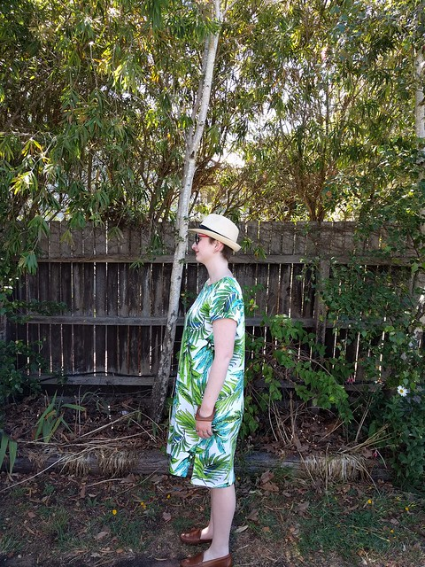 A woman stands against a garden fence, wearing a fern print dress, sunglasses and trilby hat.