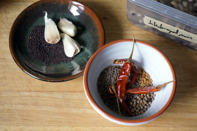 Two small dishes of spices: a shallow saucer of mustard seeds and whole garlic cloves, and a white ceramic bowl brimming with cumin, coriander, fenugreek, pepper, and whole red chiles.