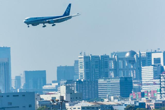 お台場の上を飛ぶ飛行機の写真