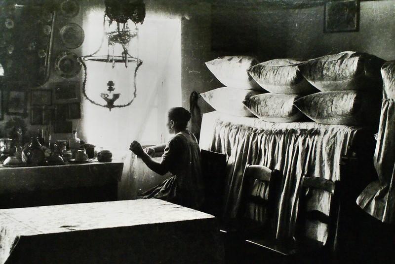 A l'intérieur d'une maison à la campagne, l'hôtesse attend elle la venue de quelqu'un ? Ou c'est elle assise après avoir ranger la pièce ?