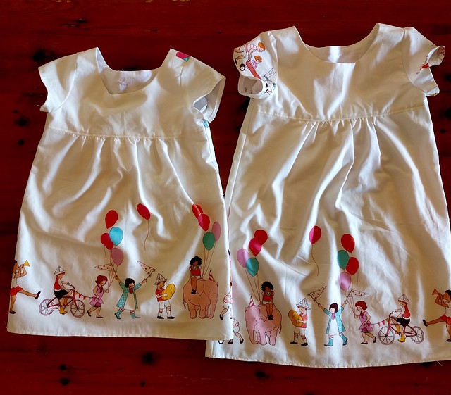 Two children's dresses in Michael Miller's Children at Play print.