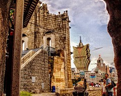 Stood under the arch next to the Na Tcha temple at dusk, to capture the view from behind the facade of the Ruins of St. Paul, tourist passing by the temple and offering prayers.  The Grand Lisboa Casino and the Bank of China is also seen in the background