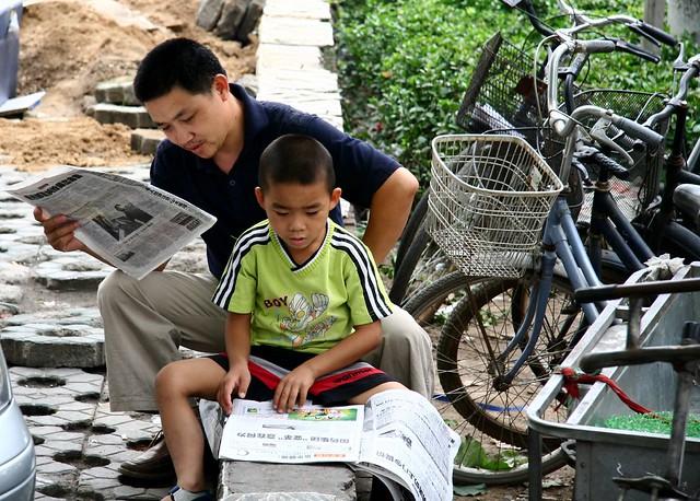 新聞を読む少年と男性(Ernop/Flickr)