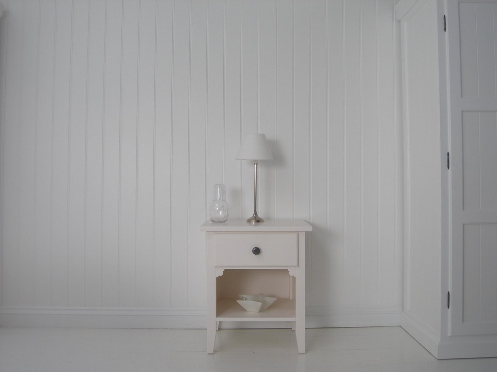 Shows A Small Cream Bedside Table By