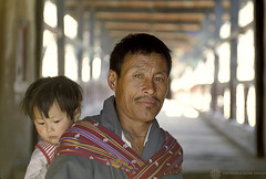 Portrait of man carrying child.  Bhutan | by World Bank Photo Collection