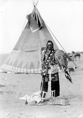 A medicine man of the Blood tribe standing in front of a teepee | by Galt Museum & Archives on The Commons