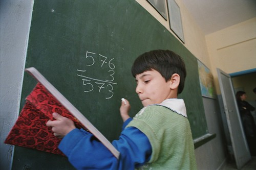 Student solving mathematic equation on blackboard | by World Bank Photo Collection
