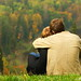 Sweet couple sitting on a hill and looking at the autumn landscape
