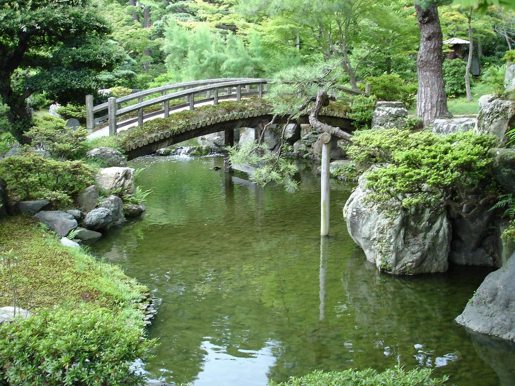 Bridge over koi pond an arched wooden bridge over a koi for Koi pond bridge