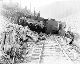 Two men standing atop wrecked locomotive on the Great Northern Railway tracks | by UW Digital Collections