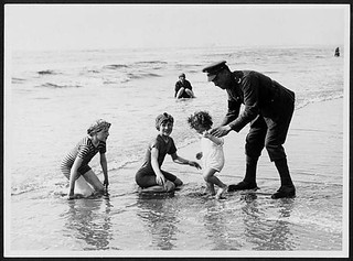 British Tommy interests himself in the happiness of the kiddies on the sands at a French coast resort | by National Library of Scotland