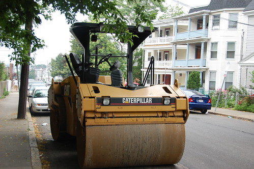 construction roller machine parked at the curb on a residential street.