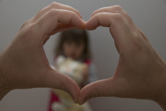 hands held in the shape of a heart over the face of a child