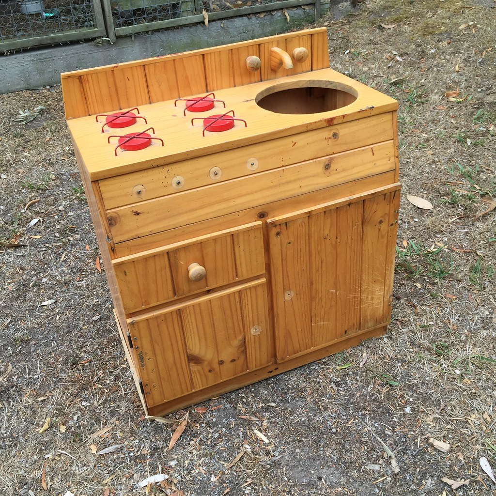 solid natural wood kitchen cupboard set with four 'burners' and a sink hole. looking a little sad and in need of love.