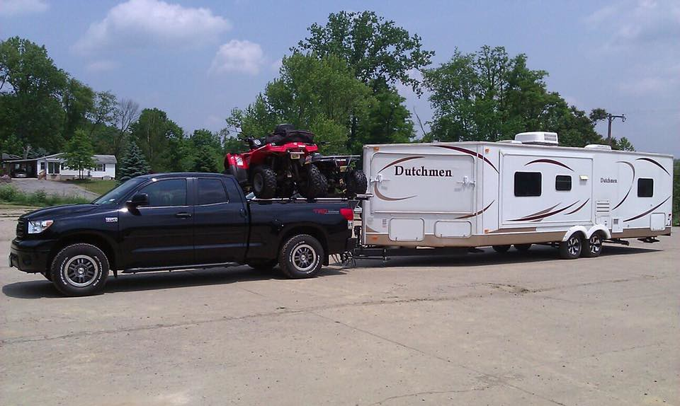 An Atv Hauler And Toyota Tundra Pulling A Camper A