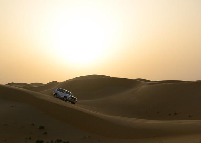 Conduciendo la cresta de una duna en el desierto de Abu Dhabi al atardecer