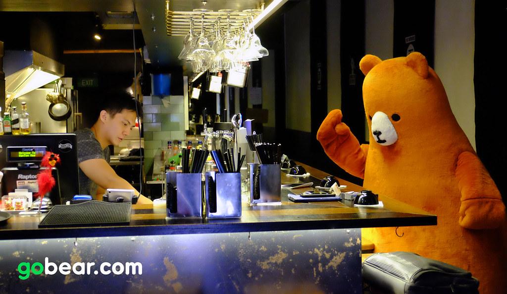 The mascot Bear from GoBear at a bar