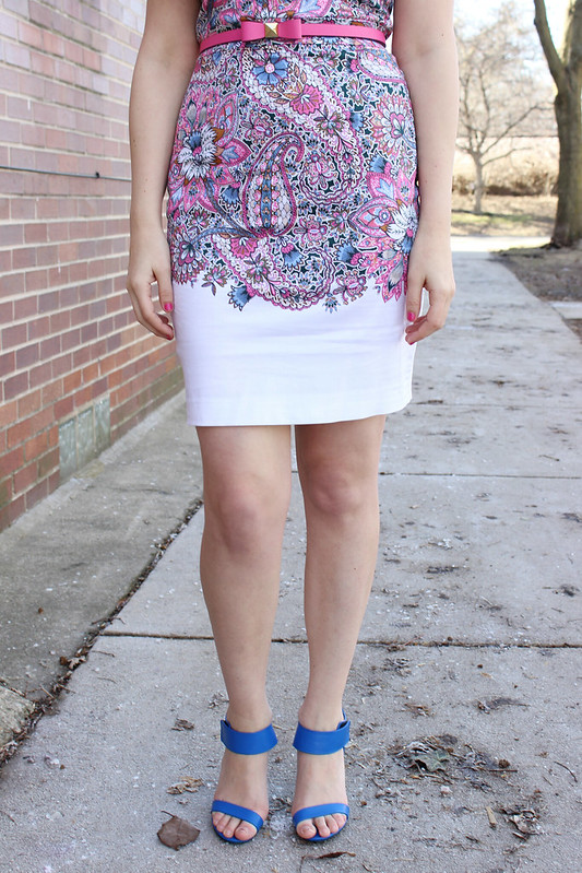 Detailed shot of the dress from the waist down. The paisley print fades out from the pattern into a solid white fabric right after the hips end.