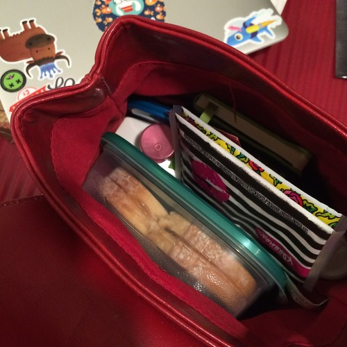 A close-up of a purse with a sandwich in tupperware at the bottom, as well as other purse acutrema (for example, tissues) around in it.