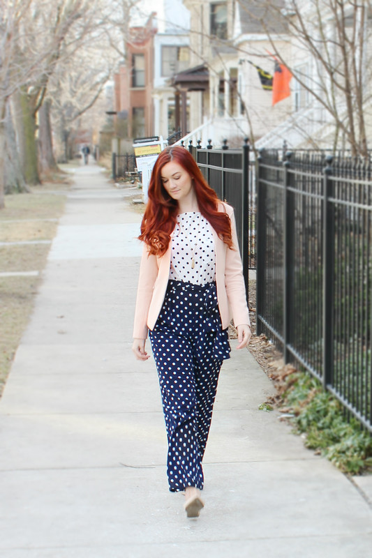Walking towards the camera. Contrasting navy and white polka dot jumpsuit with a rose quartz/blush pink blazer.