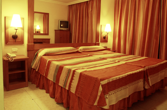 Tucked twin beds, hotel room