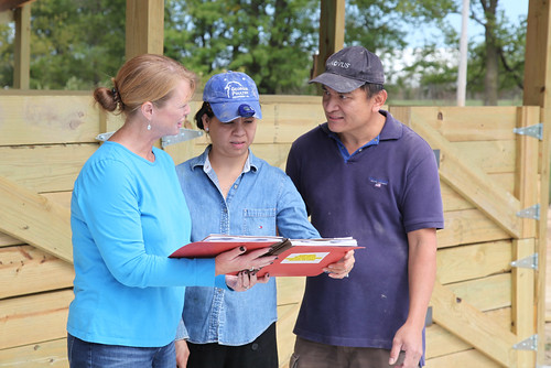 Rhonda Foster, Washington County, Ark., district conservationist, meeting with Diem and Bruce Norindr on their poultry farm