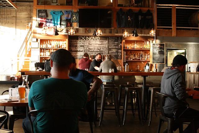 An indoor shot of Ex Novo brewing. You can see, but not read, the beer list in the far background, and there are two bartenders and four customers around.
