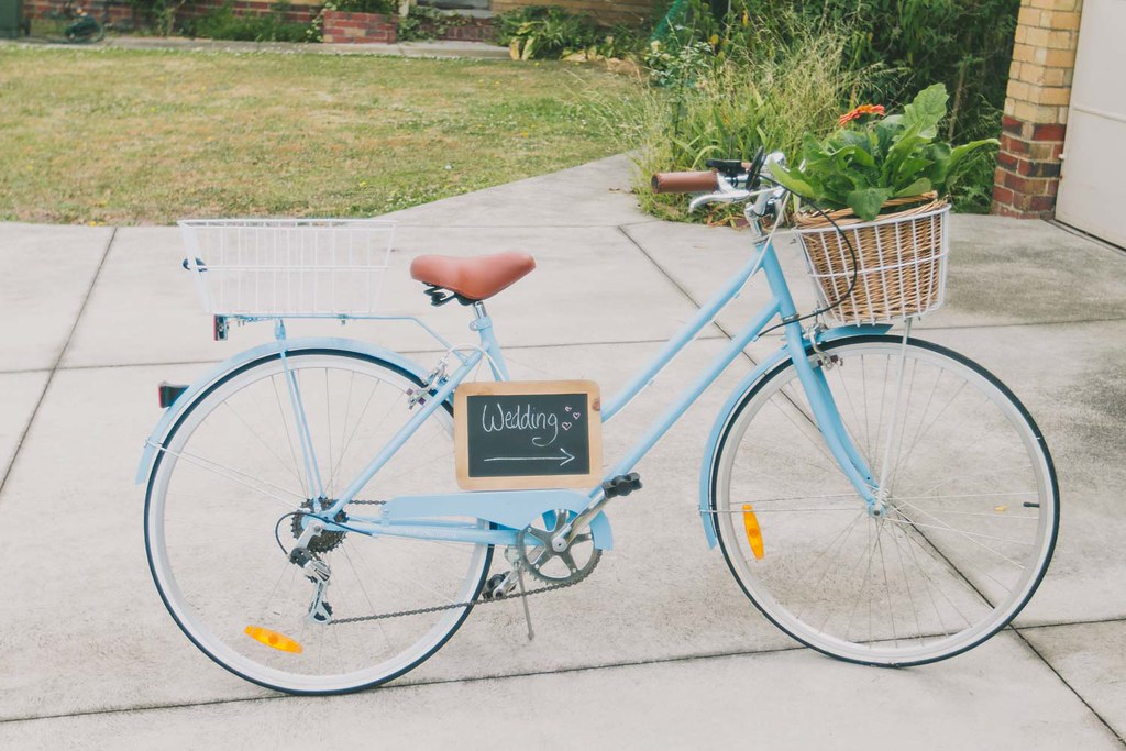 blue 'reid' cycle bicycle with hanging chalkboard sign and gerbera pots in the front basket