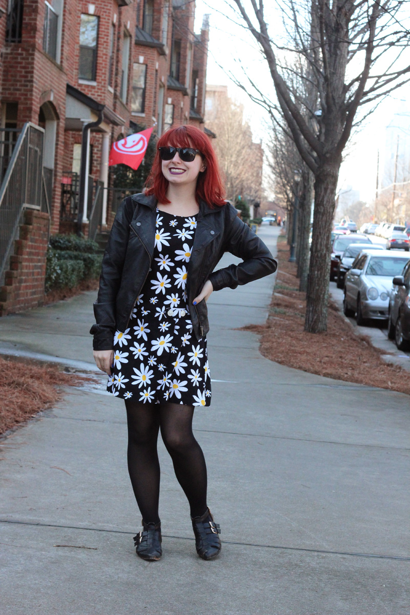 Black Leather Moto Jacket, Daisy Print Skort Romper, and Wayfarer Sunglasses