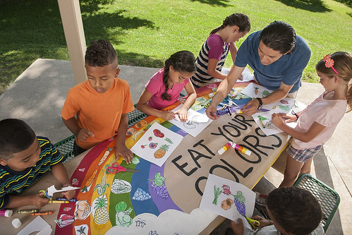 Kids and a man drawing on the Eat Your Colors theme