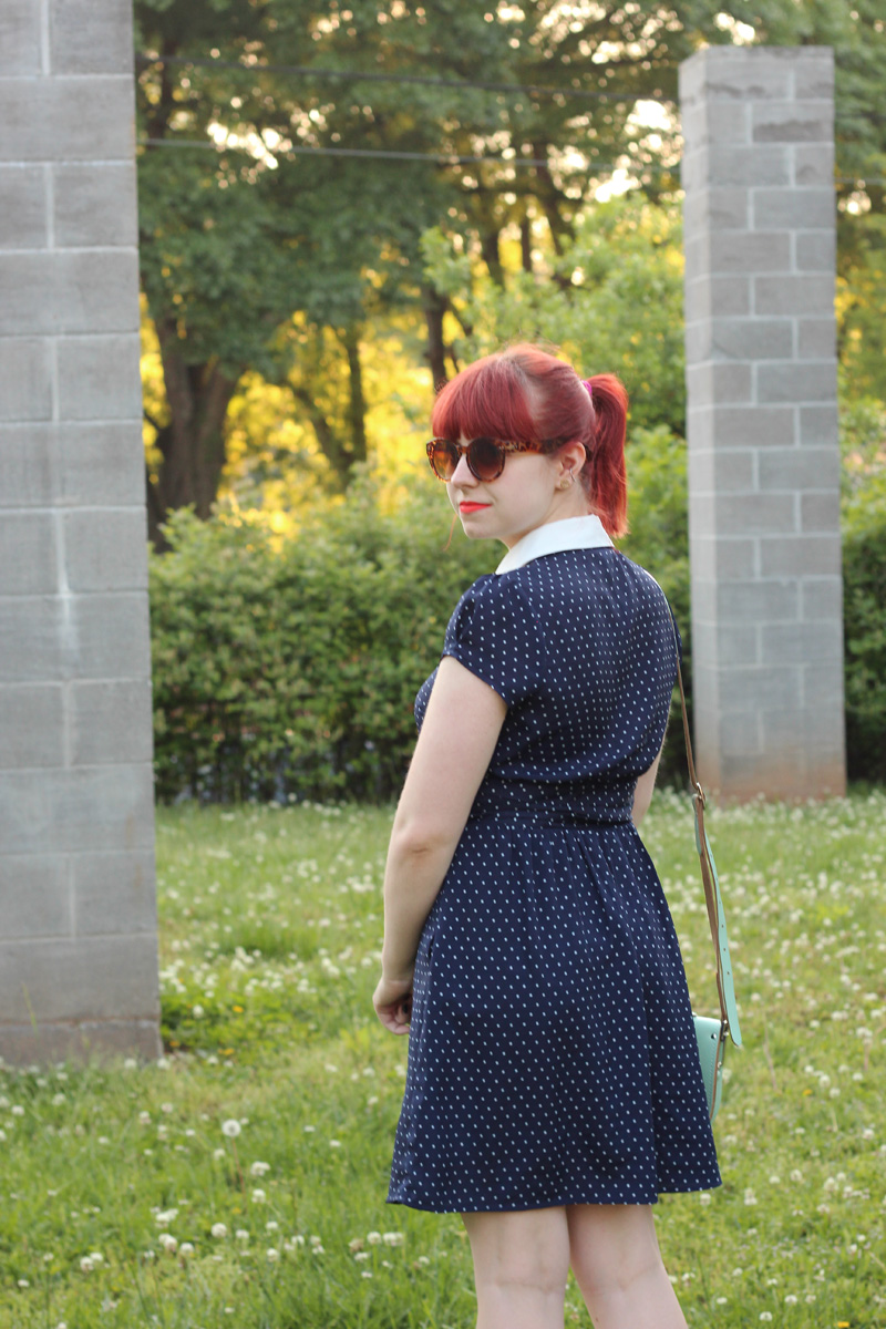 Navy Polka Dot Dress with White Collar, Red Ponytail, and Brown Sunglasses
