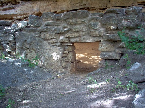 Image shows the remains of a stone wall. One of the blocks is huge, a boulder that the wall was built around. There is an opening at ground level.