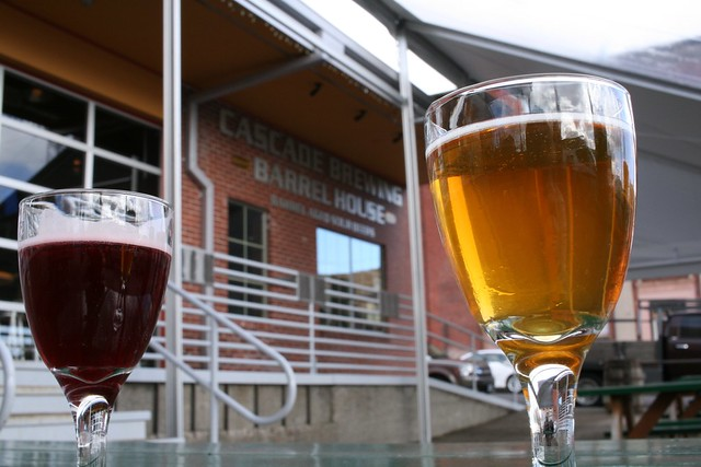 Two small goblets, one with golden beer and one with garnet beer on either side of the shot, with the name of the brewery, Cascade Brewing Barrel House, in the distance between them.