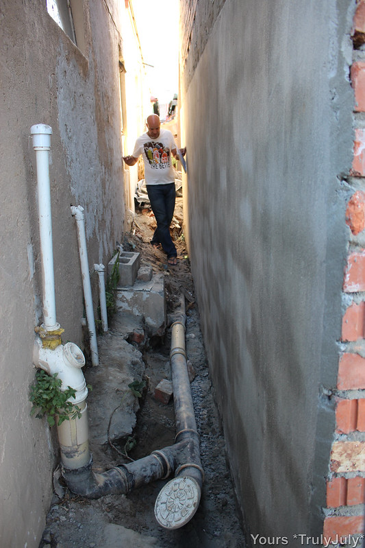 Protecting our East wall from damp turns out to be a challenge: The ground level in this service lane sits higher than our house. Also there's an interesting sewage system from our neighbour.