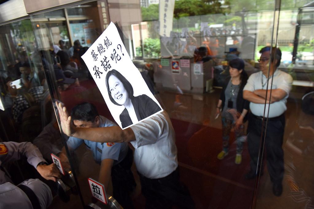 在自救會與警方衝突現場,民進黨社運部主任郭文彬(圖右)隔著人牆與玻璃門,短暫現身。(攝影:宋小海)