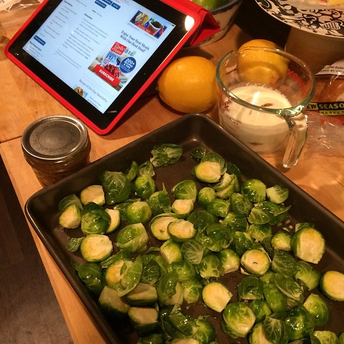 Foreground is a bunch of halved brussels sprouts in a sheet pan. Background is a measuring cup of cream, a canning jar of mustard, two lemons, and an iPad with a recipe up.