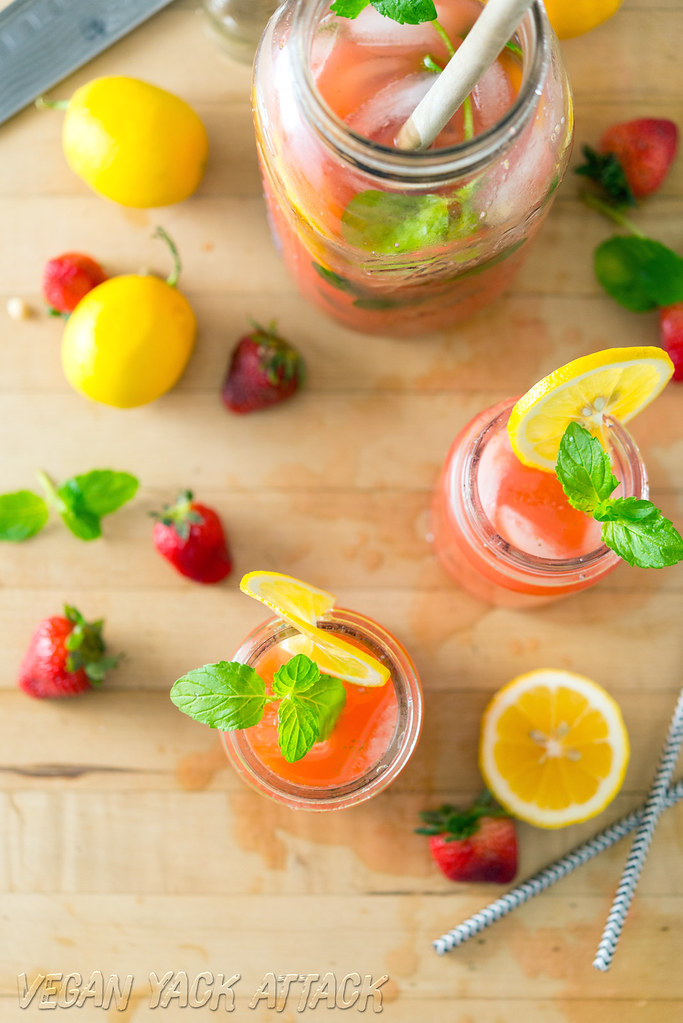 A couple of glasses of boozy mint strawberry lemonade next to a large jar of it
