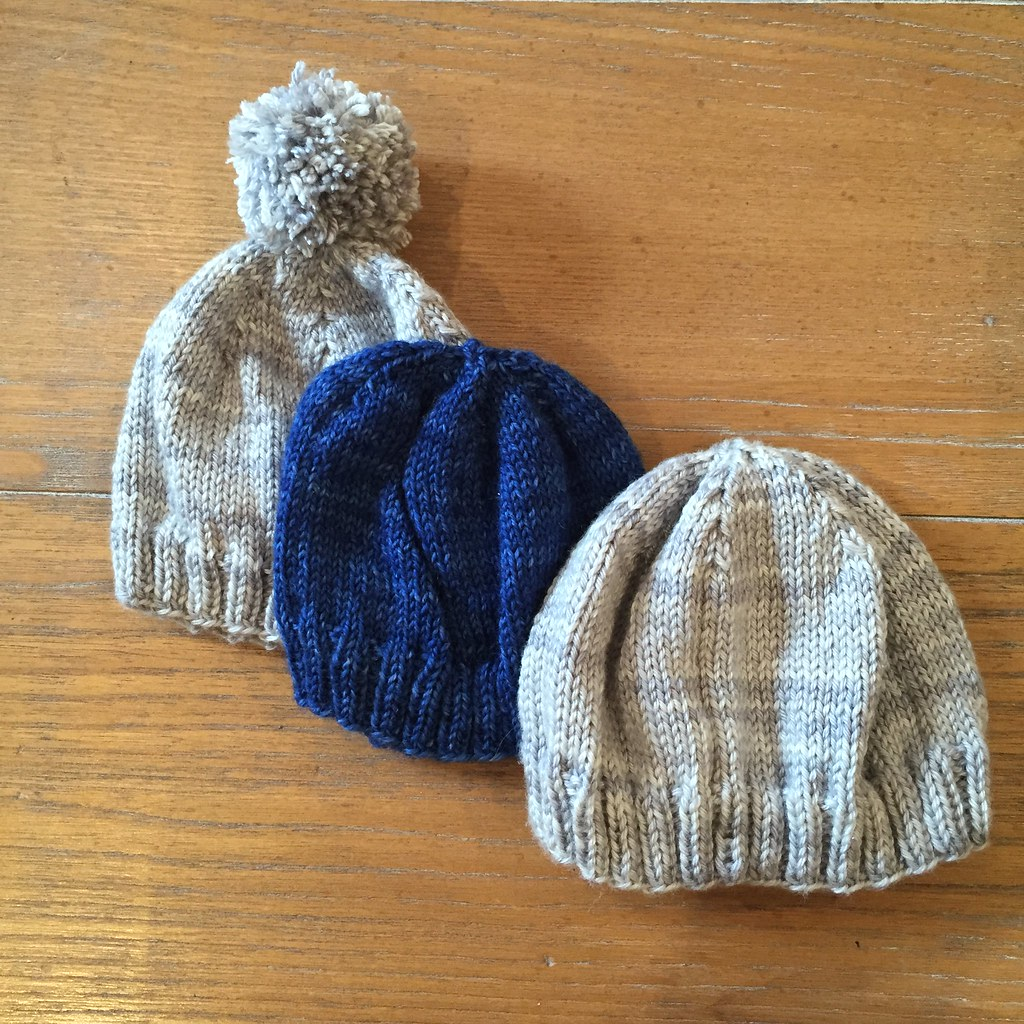 a trio of knitted baby hats, two silver (one with a pompom) knitted in sport weight and one blue knitted in fingering weight