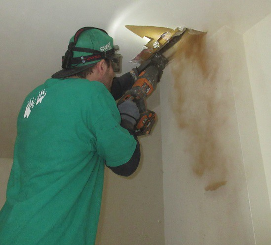 Derick cuts into the cieling near the old chimney