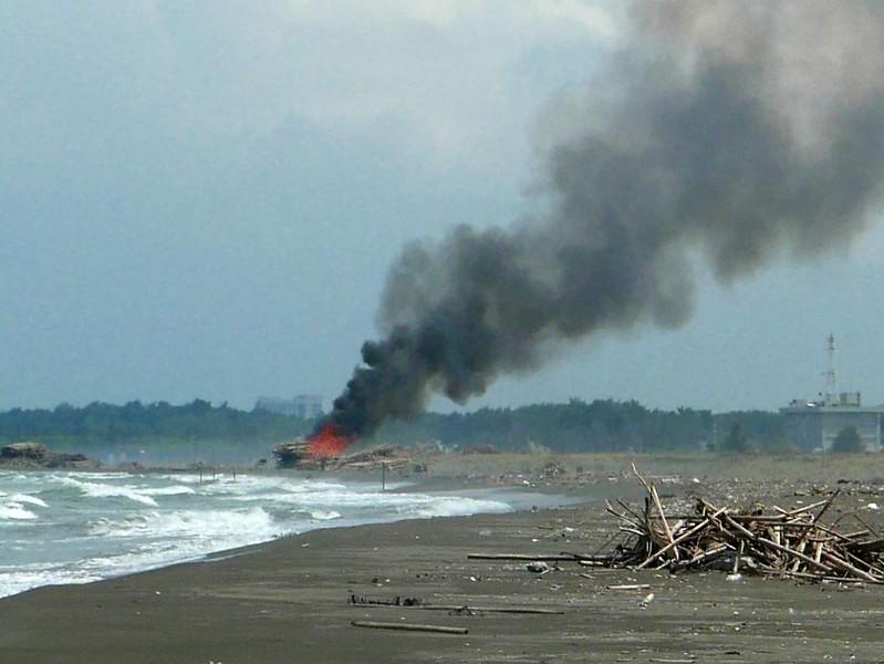 政府放任回收鐵絲的民眾把堆置海岸邊的蚵棚直接放火燒,造成極大的汙染。2015年7月3日。圖片來源:晁瑞光