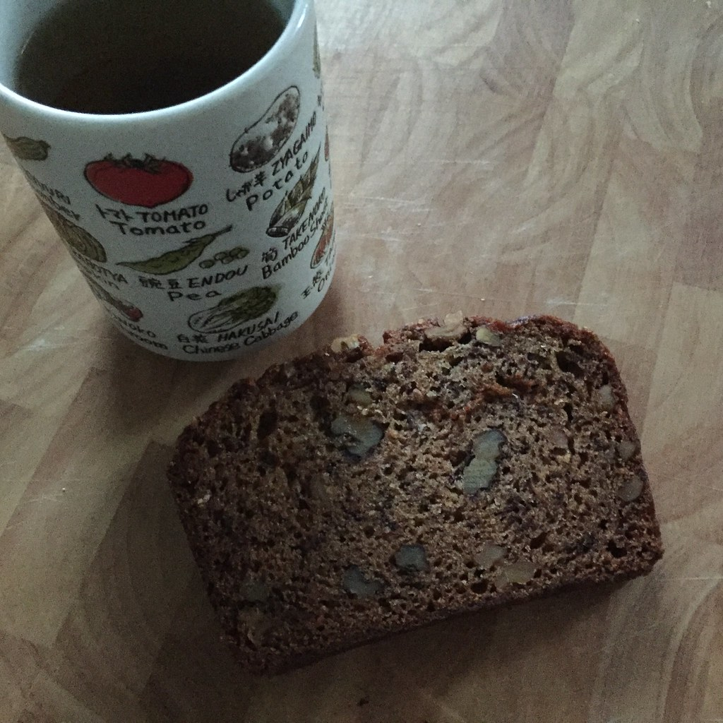 a steaming mug of green tea with a slice of banana bread with walnuts