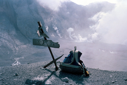 Image shows a very bedraggled target: basically a post with boards nailed horizontally to it, with round reflectors attached to the boards. The top board is knocked askew and half-torn off. A chunk has been torn off the right side of the bottom board. Someone has left a backpack beside the target. In the background is a valley filled with volcanic deposits, and tall craggy ridges stripped of all life. Steam rises from the base of the ridges.