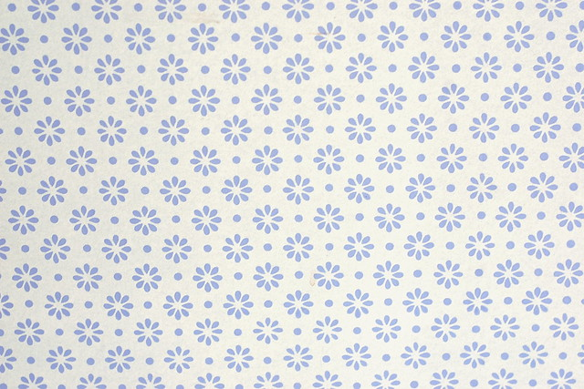 A pattern of stylised blue flowers and dots