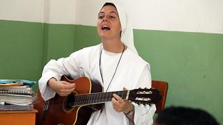 La Hermana Clare toca la guitarra, mientras enseña en Playa Prieta