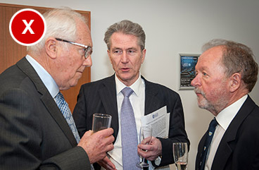 A bad example of a photo showing three men holding drinks and talking