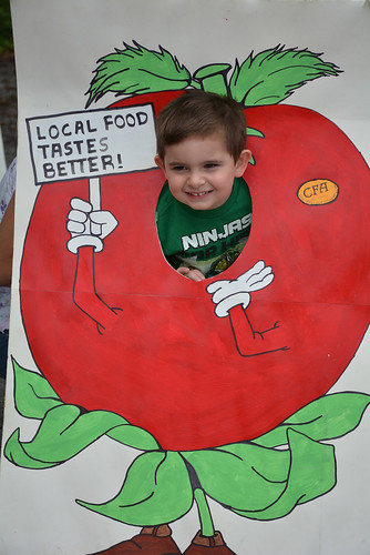 A child smiles after poking his face out in a hole on the Local Food Tastes Better sign