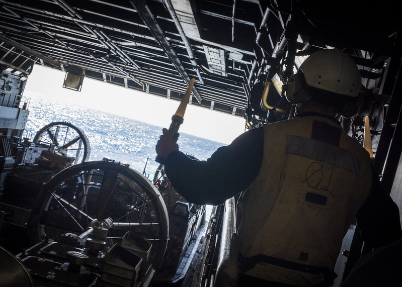 Seaman Adam White from Elgin Texas, signals a landing craft air cushion (LCAC), assigned to Assault Craft Unit (ACU) 5, to start engines aboard amphibious transport dock ship New Orleans (LPD 18).