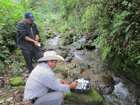 Men measuring physical characteristics and chemical parameters of water in Agua de Benita, Nicolas Romero, Michoacan, Mexico
